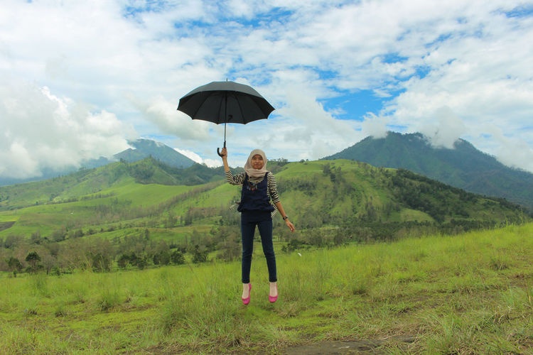 women jumping and holding umbrella Jumping People Nature Landscape Cloud Mountain Background women around the world Asian  INDONESIA Indonesian Cloud - Sky One Person Umbrella Sky Standing Plant Protection Beauty In Nature Landscape Vacations Full Length Green Color Nature Mountain Holiday Environment Adult Leisure Activity Mountain Range