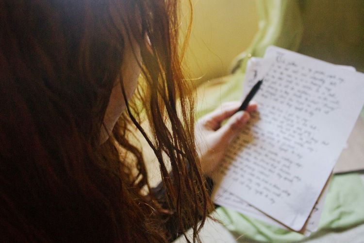 High Angle View Of Girl Reading Letters At Home