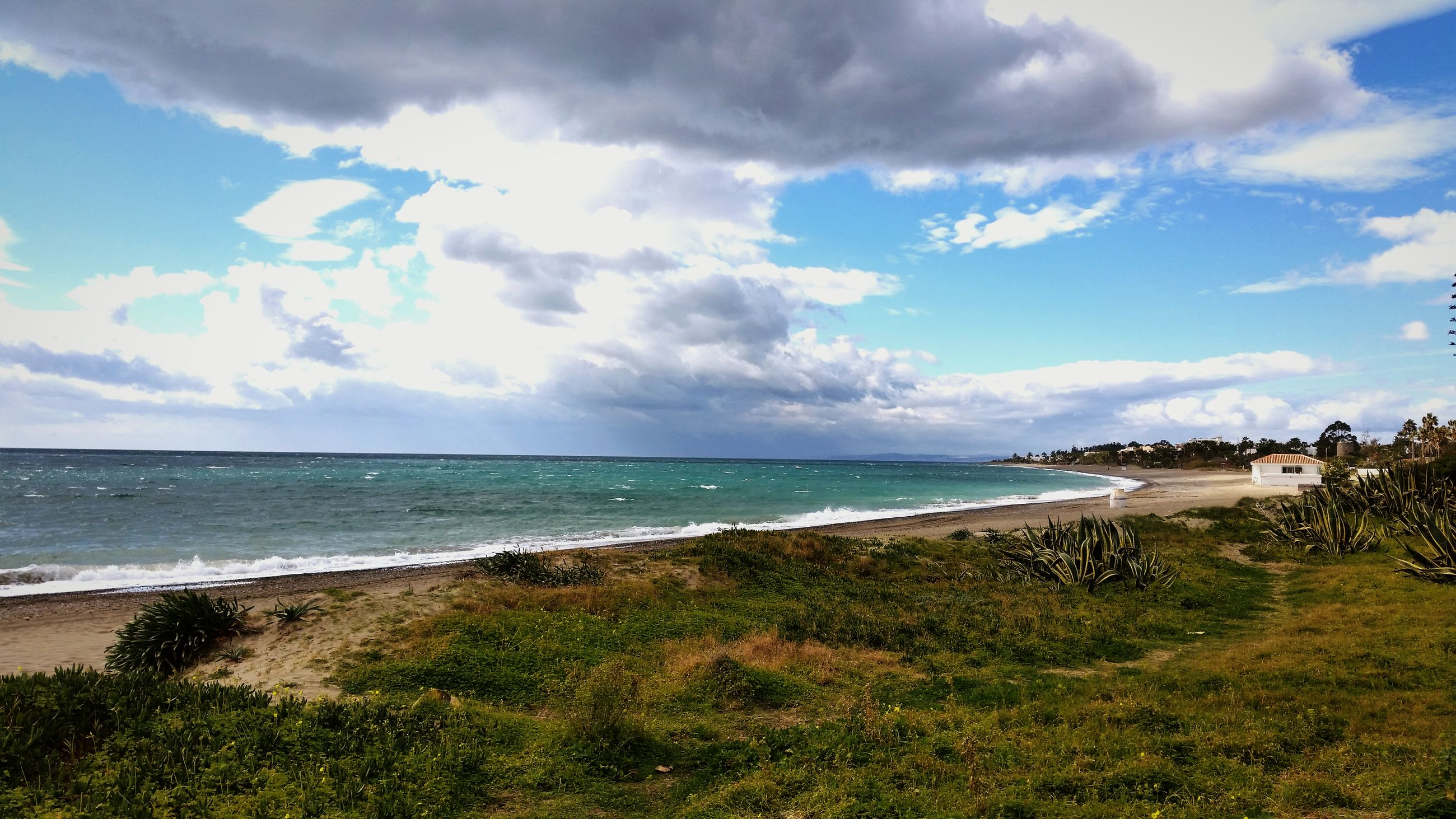 sea, horizon over water, beach, water, sky, shore, tranquil scene, tranquility, scenics, beauty in nature, sand, cloud - sky, nature, grass, coastline, idyllic, cloud, blue, cloudy, day