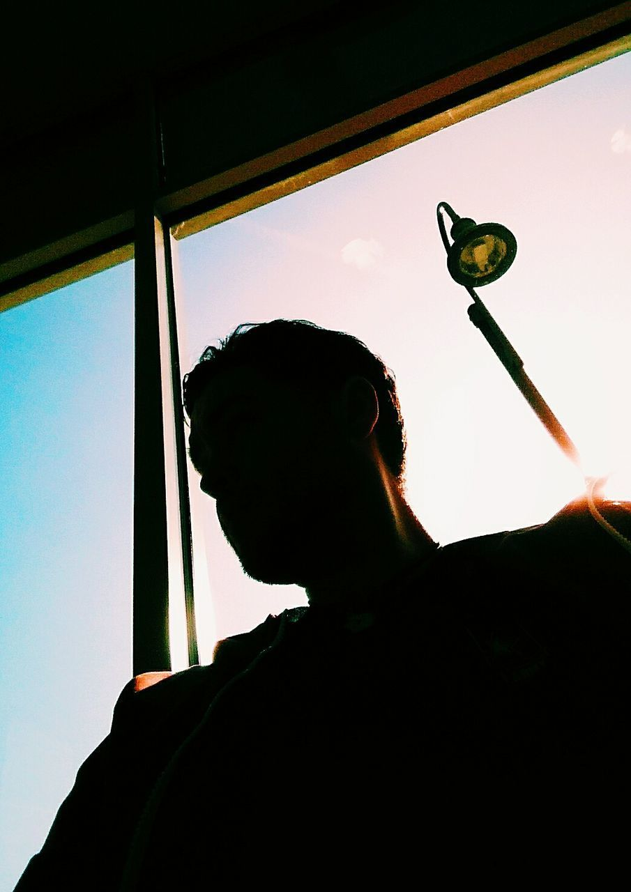 headshot, window, one person, real people, lifestyles, silhouette, sky, leisure activity, portrait, low angle view, men, nature, glass - material, vehicle interior, indoors, looking, day, sunset, contemplation