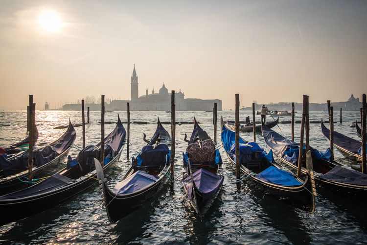 Gondolas lined up along St Mark's Bay in Venice, Italy on a hazy winters day Architecture Boat Built Structure Clear Sky Italy Mode Of Transport Nature Nautical Vessel Pier Reflection Rippled Sea Sky Sun Sunlight Sunset Tranquil Scene Tranquility Transportation Travel Venice Water Waterfront