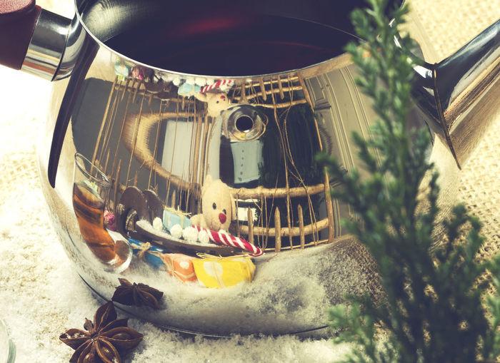 Reflection of toys on tea kettle