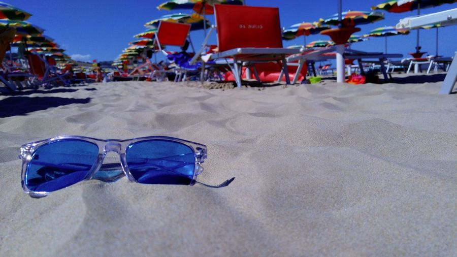 A pair of sunglasses lying on the sand of an Italian bathing facility, between the sunbeds and the colored umbrellas. Beach Blue Day Fashion Focus On Foreground Glasses Incidental People Land Nature Outdoors Personal Accessory Protection Real People Safety Sand Security Sky Sunglasses Sunlight Surface Level Water