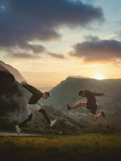 People jumping on mountain against sky during sunset