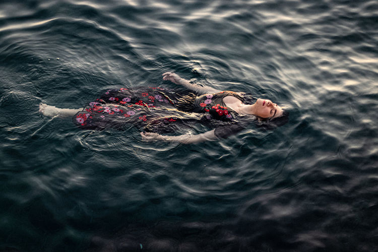 High angle view of woman floating on sea