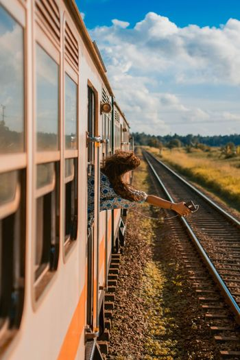 Rear view of happy woman holding mobile phone peeking through window while traveling in train