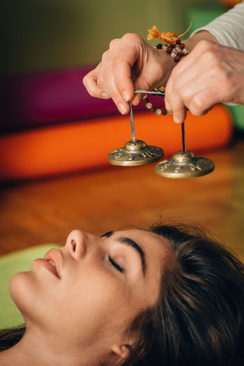 Cropped Hands Of Therapist Holding Bells By Young Woman At Spa