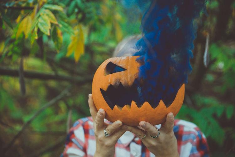 Close-up of woman hand holding smoke emitting jack o lantern outdoors