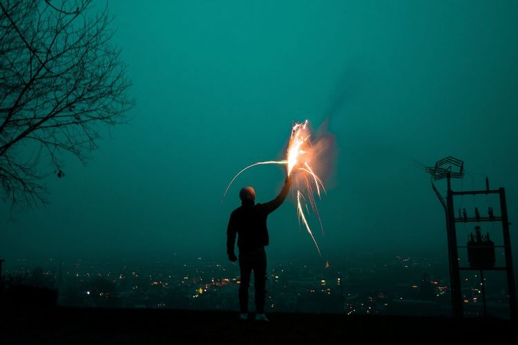 Man with arms outstretched at night