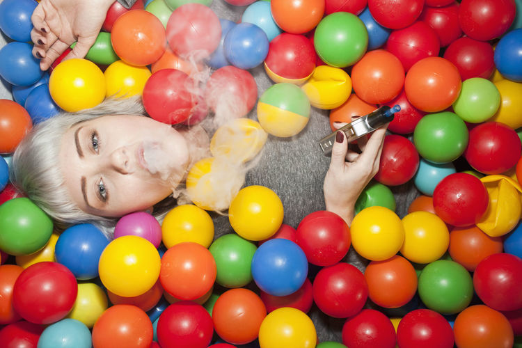 High angle portrait of smiling girl with multi colored balls