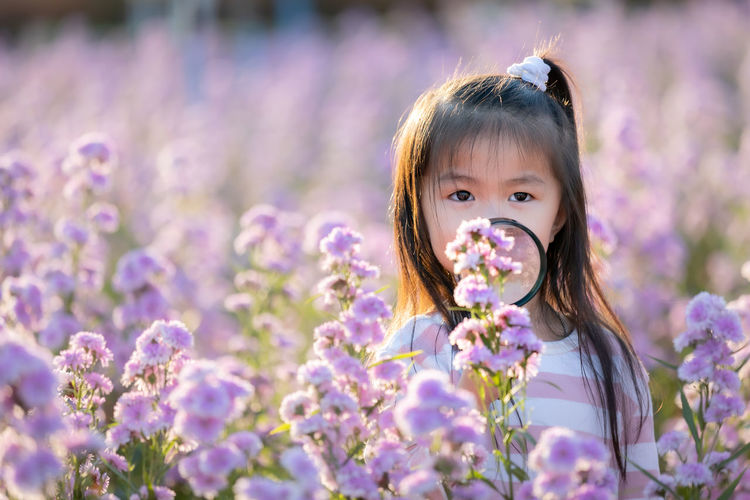 Close-up portrait of girl holding magnifying glass by purple flowering plants