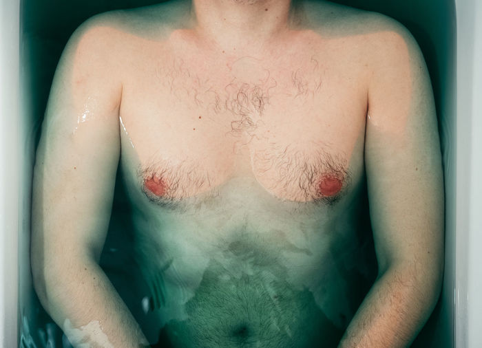 Midsection Of Shirtless Man In Bathtub