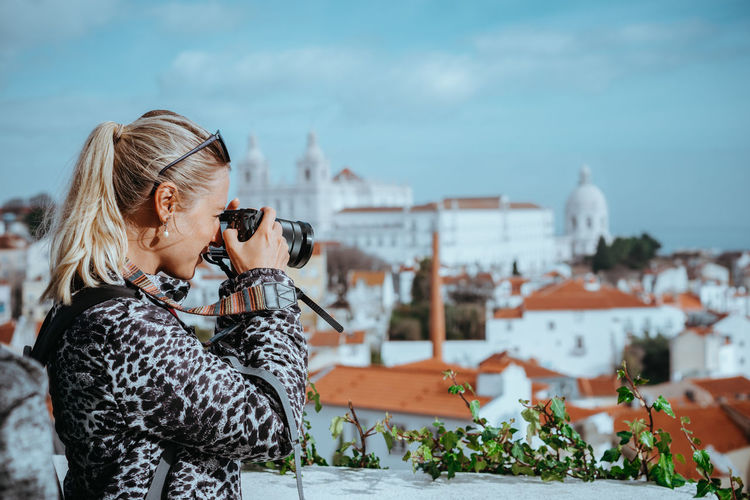 Traveler woman make a picture of Lisbon cityscape. The National Pantheon and the towels of Vicente de Fora come into view. Roofs of Lisbon Alfama Church City Downtown Landmarks Mediterranean  Pantheon Roof Tourist Adventures In The City Buildings Girl Historic Iberian Lisbon Making Pictures Multicolor Photographer Springtime Viewpoint Vintage Photo White