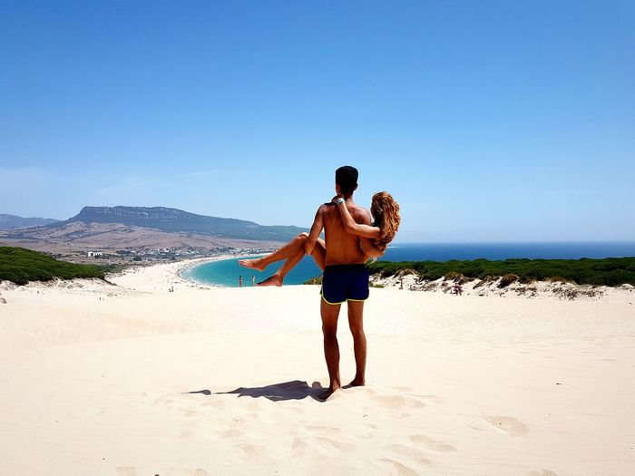 Rear View Of Shirtless Man Lifting Girlfriend While Standing At Beach Against Clear Sky