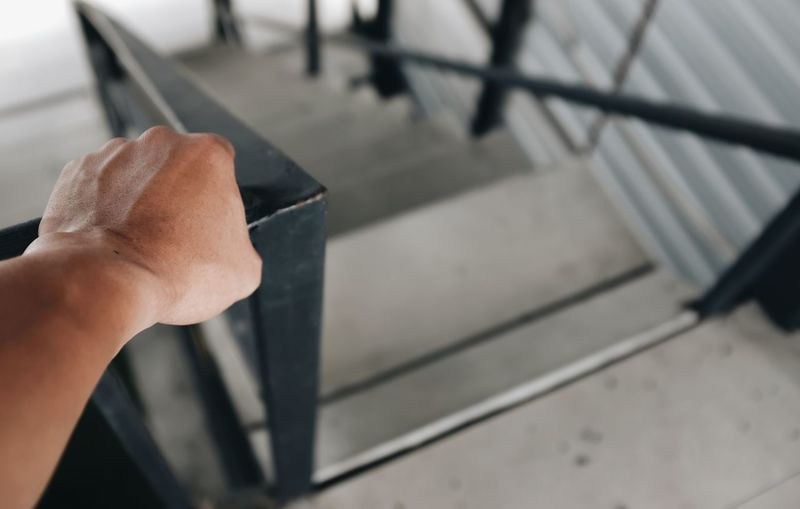 High angle view of person holding metal railing