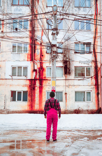 Rear View Of Man Standing Against Abandoned Building During Winter