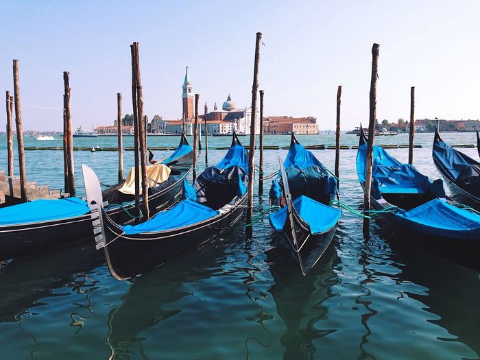 Gondolas moored by wooden posts in grand canal against sky