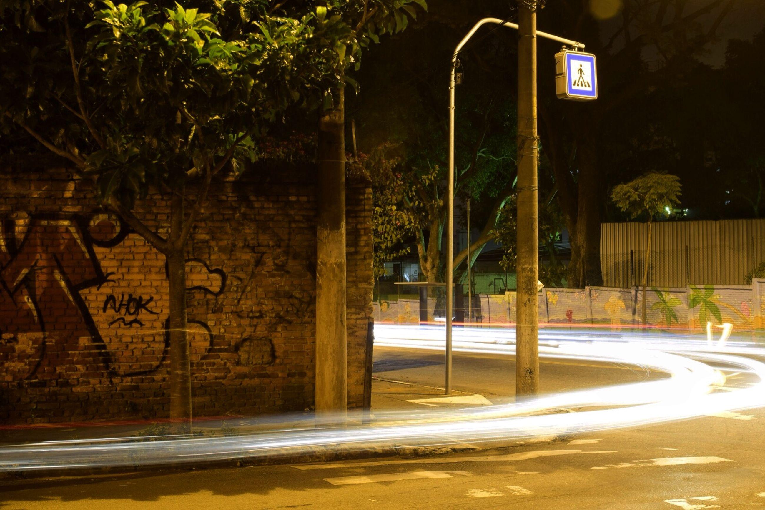 text, communication, western script, street, information sign, road sign, sign, guidance, road, street light, arrow symbol, built structure, tree, information, night, transportation, illuminated, building exterior, architecture, directional sign