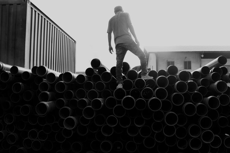 Man standing on stack of pipes against sky