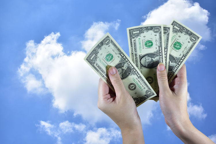 Close-Up Of Person Holding Currency Against Blue Sky