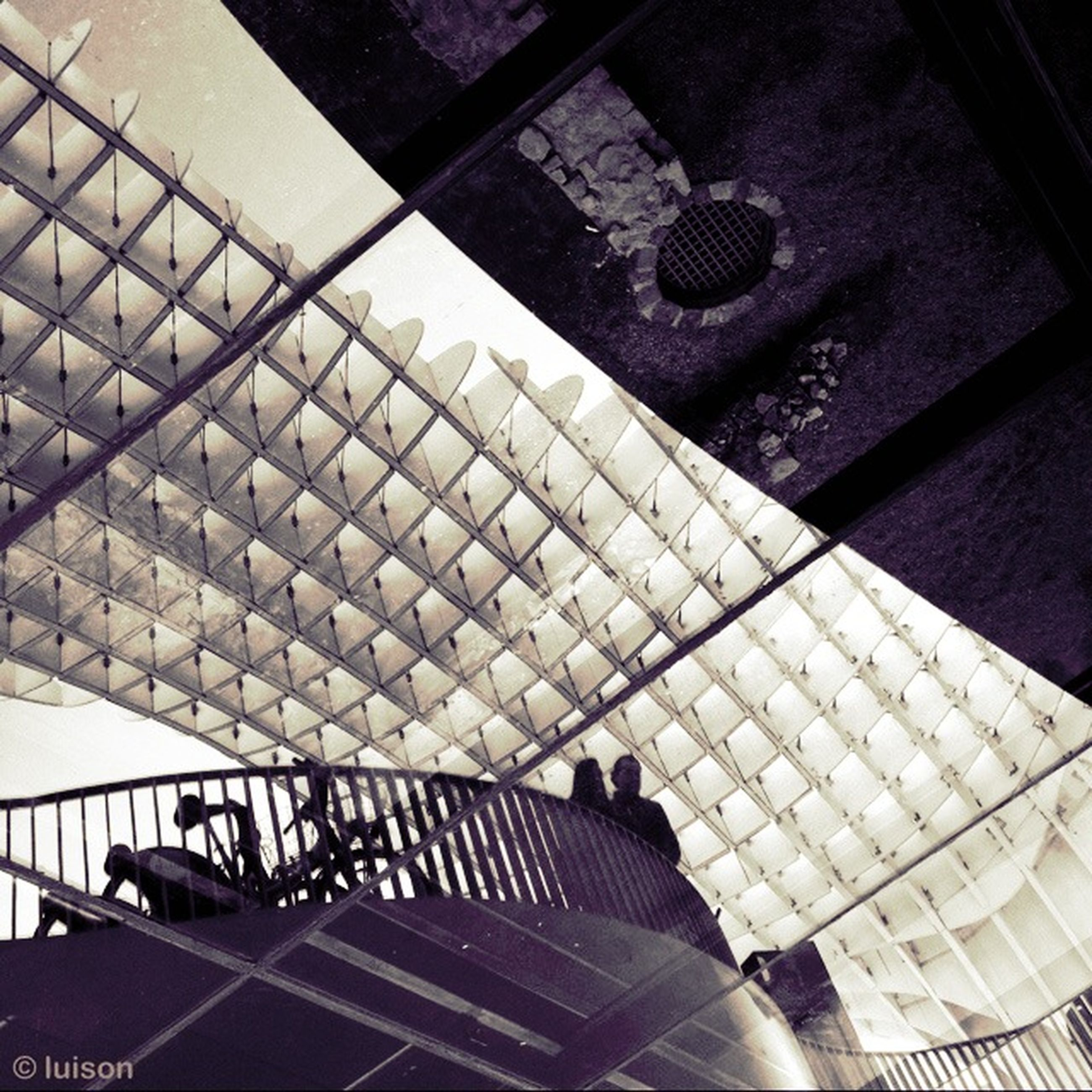 indoors, high angle view, architecture, built structure, shadow, wall - building feature, window, sunlight, tiled floor, glass - material, metal, no people, railing, pattern, day, reflection, flooring, steps, modern, tile