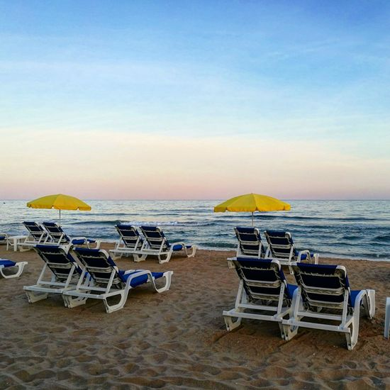 Beach Chair Sea Sand Outdoor Chair Horizon Over Water No People Table Summer Relaxation Vacations Tranquility Tranquil Scene Sky Sunset Scenics Nature Beauty In Nature Day Outdoors castelldefels spain