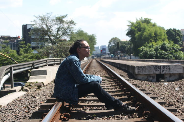 Side View Of Young Man Sitting On Railroad Track Against Sky
