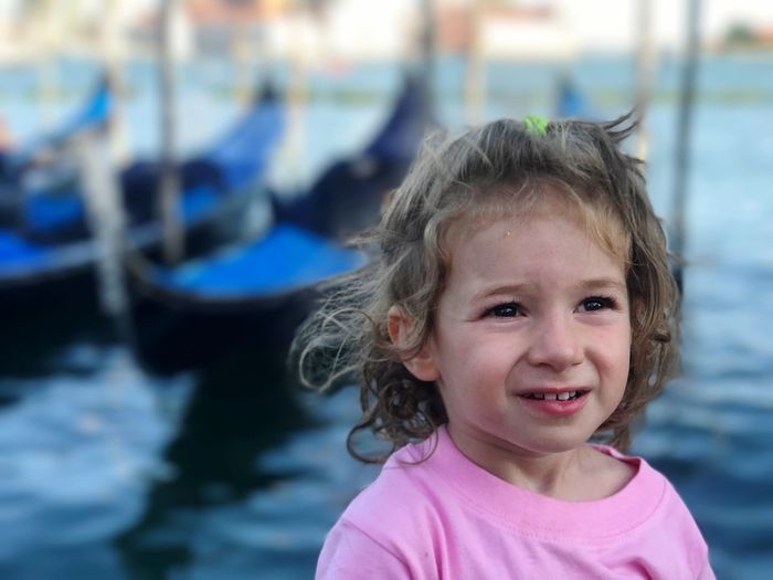 Close-up of girl looking away while standing against grand canal