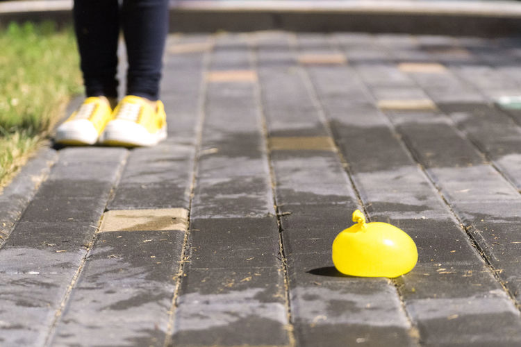 Low section of girl wearing yellow shoes throwing water bomb