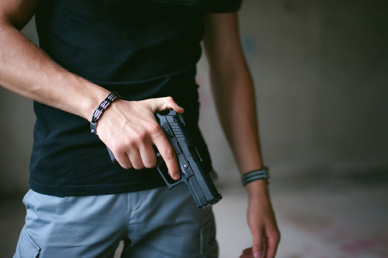 Close-up Crime Danger Day Gun Handgun Holding Human Hand Men Midsection One Person Outdoors Real People Standing Weapon