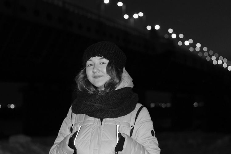 Portrait of happy young woman in warm clothing standing against illuminated bridge