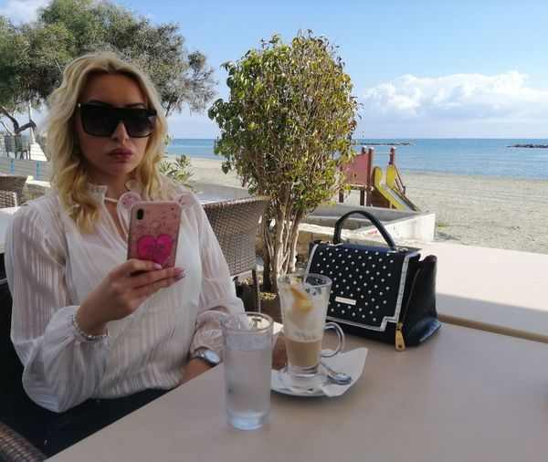 Woman wearing sunglasses using smart phone while sitting at outdoor restaurant