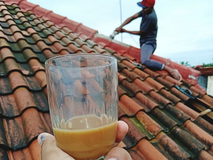 Cropped hand holding tea with man working on roof in background