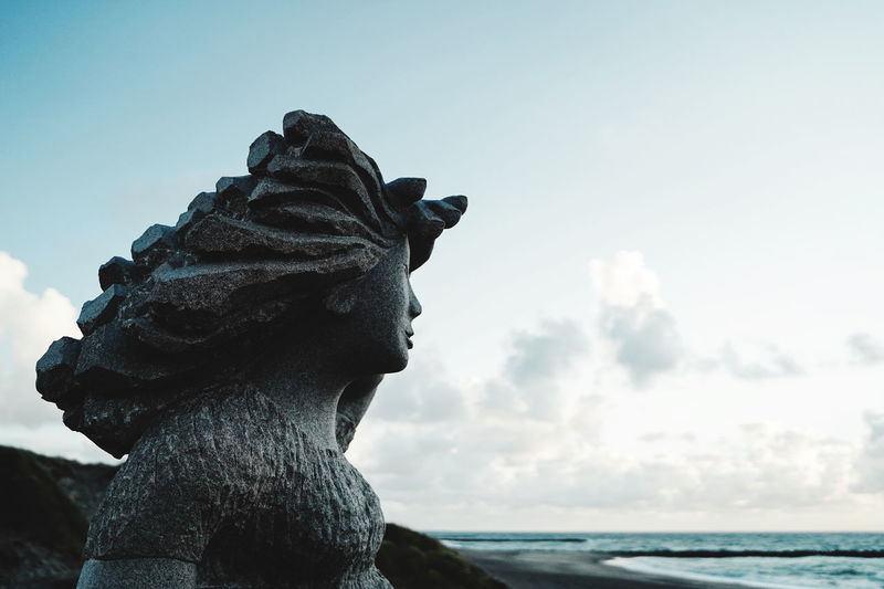 Close-up of statue against sea against sky