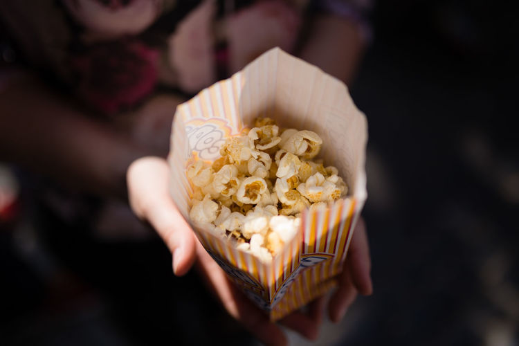 Cloe-up of popcorn in a paper bag Bag Cinema Close Up Close-up Film Food Food And Drink Freshness High Angle View Holding Human Hand MOVIE One Person Paper Popcorn Popcorns Sweet Food Theater Unhealthy Eating Women