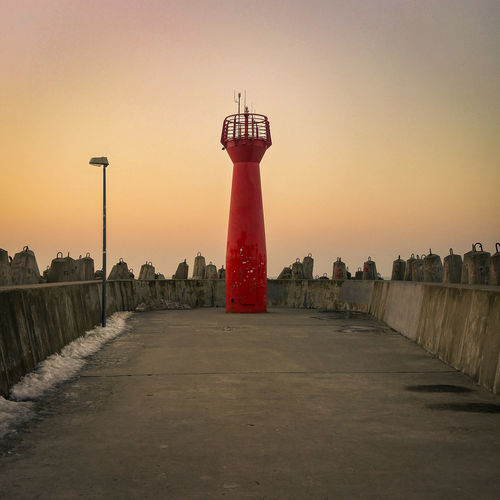 Lighthouse against clear sky during sunset