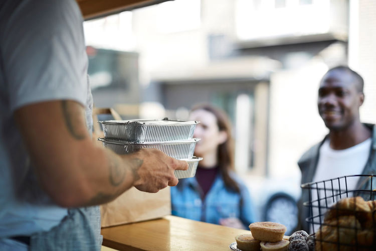 Midsection of man drinking coffee in cafe