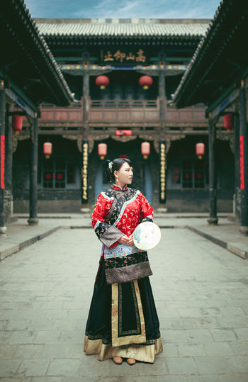 Young woman standing at courtyard of temple