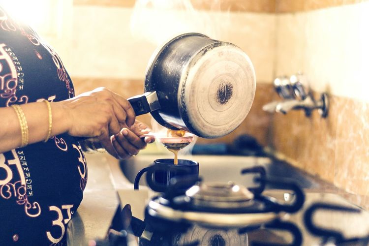 Midsection Of Woman Straining Tea In Kitchen