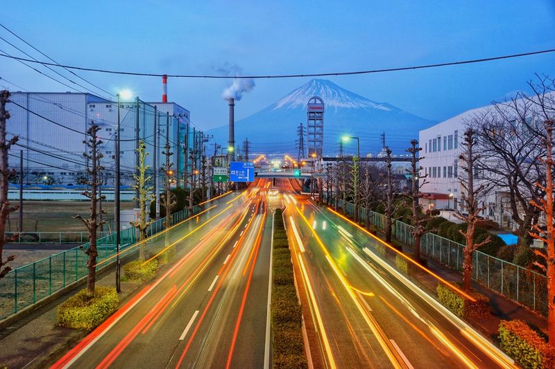 Light trails on road in city against sky