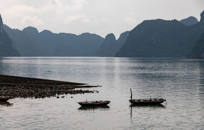 Cat Ba Island , Vietnam with small boats in foreground Water Nautical Vessel Mountain Transportation Mode Of Transportation Scenics - Nature Beauty In Nature Tranquility Tranquil Scene Sky Nature Lake No People Day Non-urban Scene Mountain Range Idyllic Waterfront Outdoors Rowboat Vietnam Vietnamese Vietnam Trip Cat Ba Island Boat ASIA