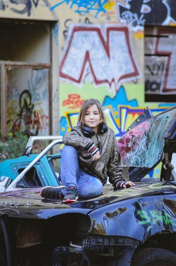 Portrait of smiling woman sitting against graffiti