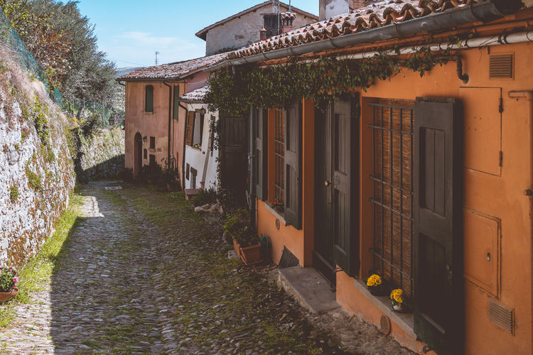 Street of a small village of Italy. Architecture Built Structure Building Building Exterior House Footpath The Way Forward Direction No People Residential District Day Nature Plant Outdoors City Street Tree Town Alley Narrow Cobblestone Village Life Italy