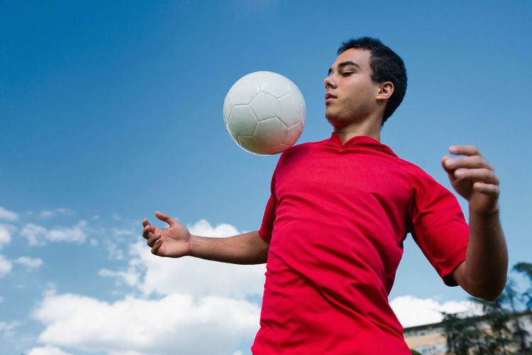 Low Angle View Of Man Playing With Soccer Ball Against Blue Sky