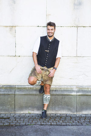 A young male poses to the camera whilst leaning against a wall at the Octoberfest Festival in Munich, Germany Adult Brown Hair Caucasian City Content Day European  Germany Good Looking Happiness Happy Individual Leaning Lederhosen Małe Legs Munich One Person Outdoors Portrait Pose Smiling Theresienwiese Tracht Vertical Young Adult