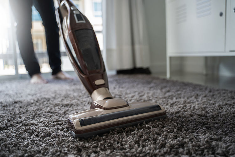 Low section of person cleaning carpet with vacuum cleaner
