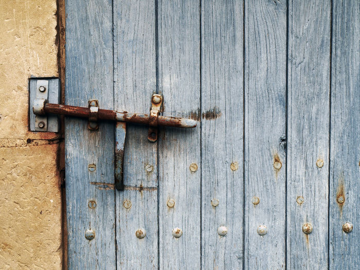 Close-Up Of Rusty Latch On Closed Wooden Door