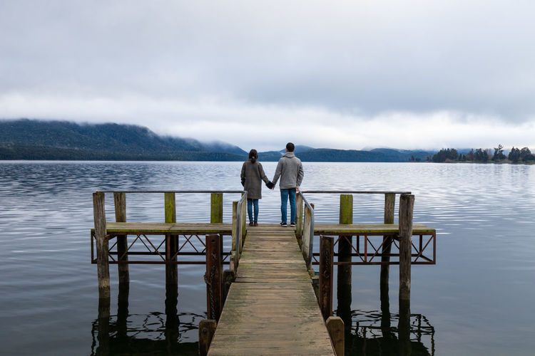 Rear view of men standing on pier over lake against sky