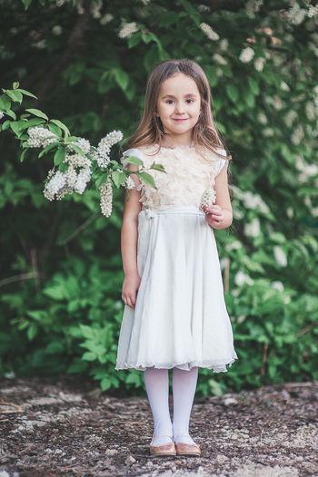 Portrait of smiling girl standing against plants