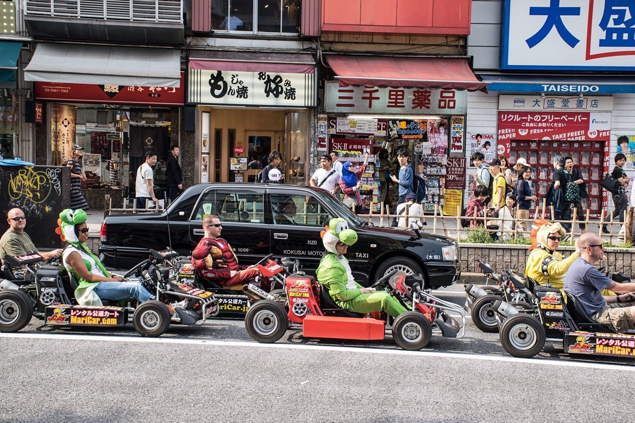 transportation, land vehicle, car, building exterior, street, mode of transport, real people, architecture, built structure, outdoors, day, city, sports race, men, large group of people, competition, racecar, crowd, people